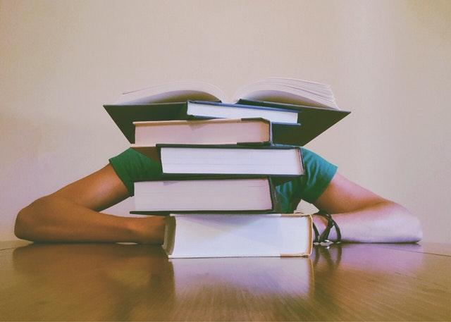 Žena sedí pri stole s hlavou na stole za kopou kníh.jpg