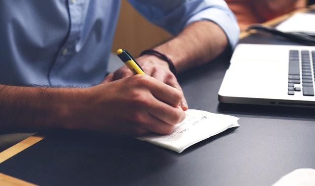 Muž v modrej košeli sedí pri stole a píše na papier poznámky.jpg